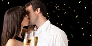 Kissing Couple Celebrating New Year with Champagne Flutes